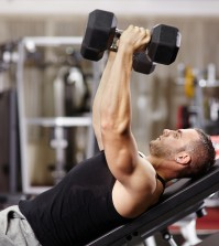 Athletic young man laid on back working his chest with heavy dumbbells